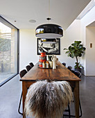 Black ceiling lamps above wooden table in modern dining room