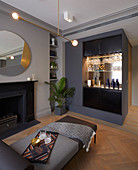 Bar in glamorous, grey living room with open fireplace