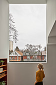 Woman standing below large window in modern, architect-designed house
