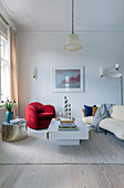 Roter Sessel, goldener Beistelltisch und beiges Sofa im Wohnzimmer