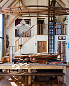 Double height dining room with 1940s fire ladder and model ships hulls with old canoe frame in Sussex barn conversion