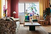 Polstersofa mit Blumenmuster, Couchtisch und bunte Vorhänge im Wohnzimmer