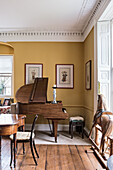 Baby grand piano in dining room with rocking horse and framed paintings of warriors