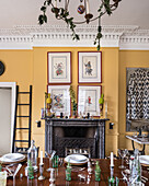 Framed hand painted warriors hang above a marble mantlepiece, decorative pineapples adorn antique urns and the table