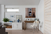 Artwork above wooden desk with sheepskin on chair