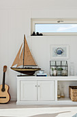 Wooden sailing boat with crab painting and guitar