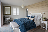 Blue quilt on double bed with wood cladding in coastal home