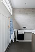 Striped towel and backbrush beside freestanding bath in coastal home