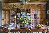 Decorative chinaware on antique wooden dresser with table and chairs in restored 16th century farmhouse