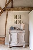 Schneiderpuppe auf Anrichte, darüber botanische Bilder im restaurierten Bauernhaus