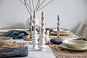 Arrangement of artistically twisted, pastel-coloured candles on table