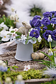 Small Easter decoration with flowers of filled primrose, pushkinia, Cherry plum blossoms, and grape hyacinth, Easter bunny, and Easter eggs