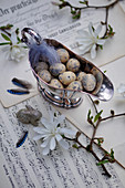 Easter eggs and feathers in silver sauce boat, magnolia branches, Easter bunny and jay feathers