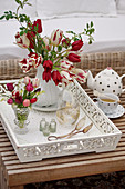Vase of tulips, wild roses and lily-of-the-valley on white wooden tray