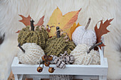 Knitted pumpkin decorations and autumn leaves