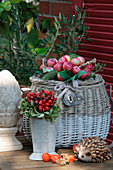Autumnal still-life arrangement of apple wreath on basket, bouquet of rose hips, hedgehog ornament and physalis seed pods