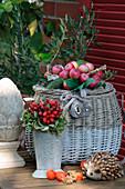 Herbstliches Stilleben mit Apfelkranz auf Korb, Hagebutten-Strauß, Dekozapfen, Dekoigel und Lampions