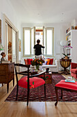 Red chairs, antique chest of drawers, chests used as coffee table and sofa in living room; woman in background
