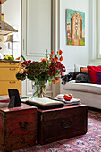 Anitke chests with bouquet of flowers as coffee table in living room