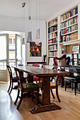 Antique chairs around wooden table in front of bookcase