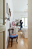 Room with antique chair and white modern furniture; girl with cat in the background