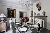 Deer's head above fireplace in dining room with glass chandelier