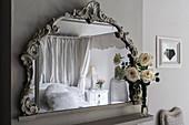 Kissen auf dem Himmelbett reflektiert im Spiegel mit geschnitztem Rahmen und weißen Rosen