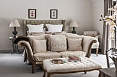 Cream two seater sofa at foot of double bed with lamps at bedside