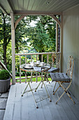 Wrought iron table and chairs on Victorian terrace, set in woodland, Surrey, England