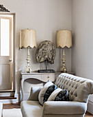 Buttoned sofa with pair of lamps and antique bust on console