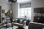 Buttoned sofa at sunlit window with lamps and sculpture on console