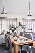 Pendant lights and closed Venetian blinds with wooden table