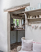 Hearts hang on wall mounted shelf with view to kitchen