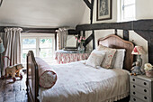 Vintage fabrics in room with antique French bed and original wooden floorboards and beams