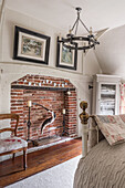 Red-brick fireplace with antique chair upholstered