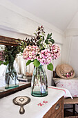 Pink hydrangeas with vintage hand mirror and vase from Garden Trading reflected in antique mirror