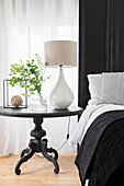 Round, antique bedside table with table lamp and leafy branches