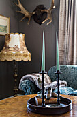Tray with candles on antique coffee table, floor lamp and antlers in the background