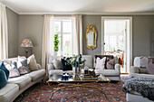 Upholstered suite around antique glass table and gilt-framed mirror in living room with grey walls
