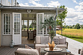View from terrace with rattan furniture into the conservatory