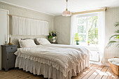 Double bed in the bedroom with nostalgic wallpaper, curtains and frills