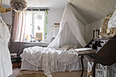 Bed with canopy next to antique secretary in girls' bedroom