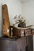 Violin case and suitcase on cabinet
