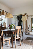 Rustic dining area, mirror, doorway with door curtain and dresses hung from pole