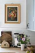 Bouquet of flowers, kitchen utensil, vintage scale on kitchen cupboard, flower picture above it