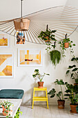 Designer lamp, many green plants and modern art on the wall in the living room