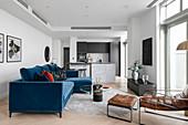 Blue velvet sofa in a modern, open-plan living room with designer style
