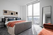 Modern bedroom in gray tones with orange accents
