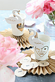 Swan clips on paper cups on paper rosettes for party table