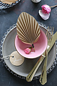 Paper fan in dish decorating place setting on table